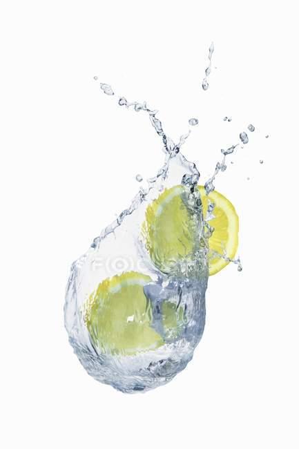 Splash de agua con rodajas de limón - foto de stock