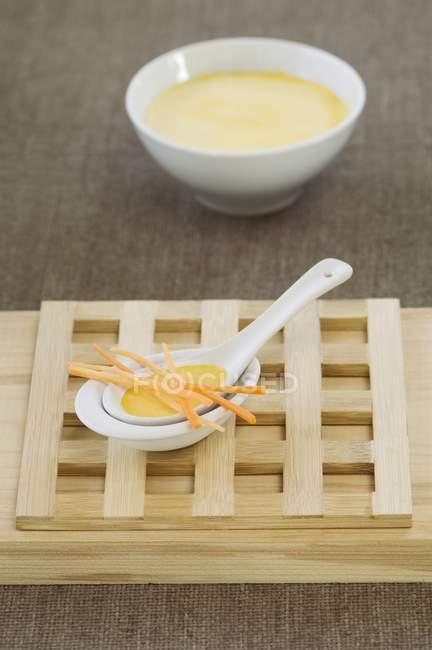 Морковный суп с морковными полосками в миске — стоковое фото