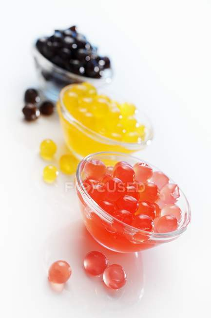 Closeup view of colored cornflour balls for bubble tea in three glass bowls — Stock Photo