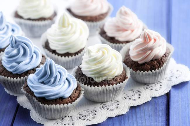 Chocolate cupcakes decorados com creme colorido — Fotografia de Stock
