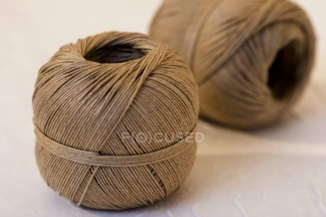 Vista de cerca de dos bolas de cuerda en la superficie blanca - foto de stock