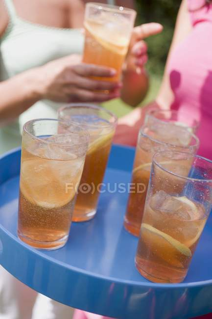Closeup view of iced tea in glasses on tray with women on background — Stock Photo