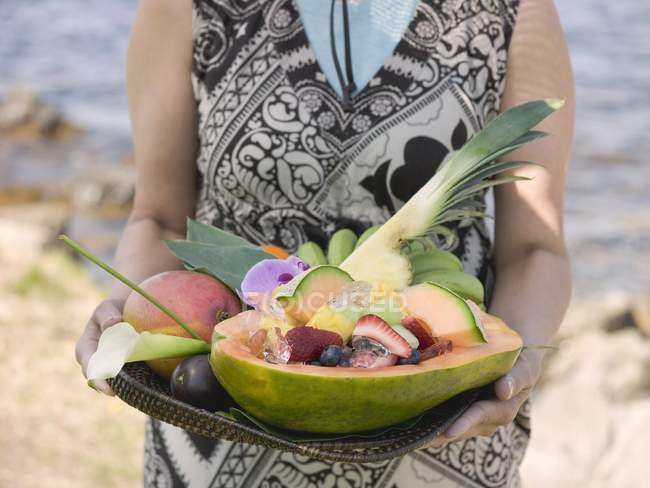 Woman holding tray of exotic fruits — Stock Photo