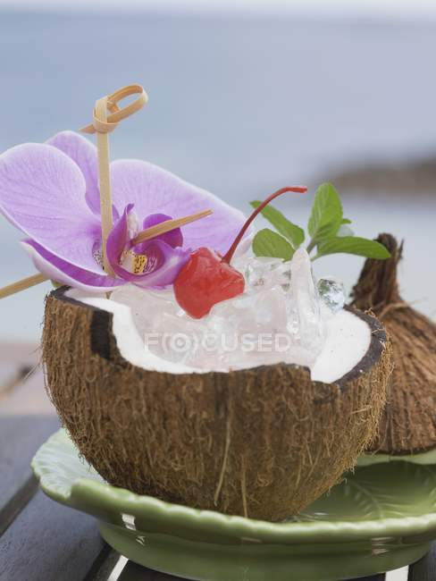 Opened coconut with mint and orchid — Stock Photo