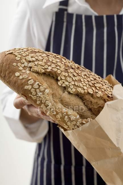 Femme mettre du pain dans le sac — Photo de stock