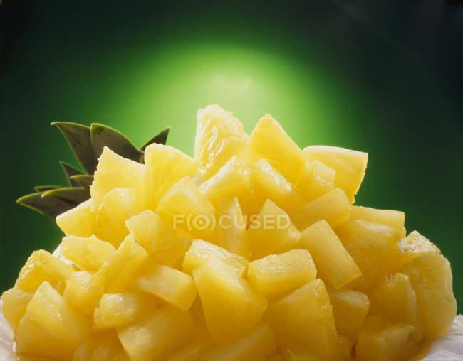 Pineapple chunks with pineapple leaves — Stock Photo