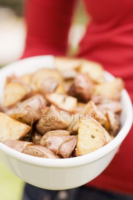 Femme tenant un plat de pommes de terre au romarin — Photo de stock