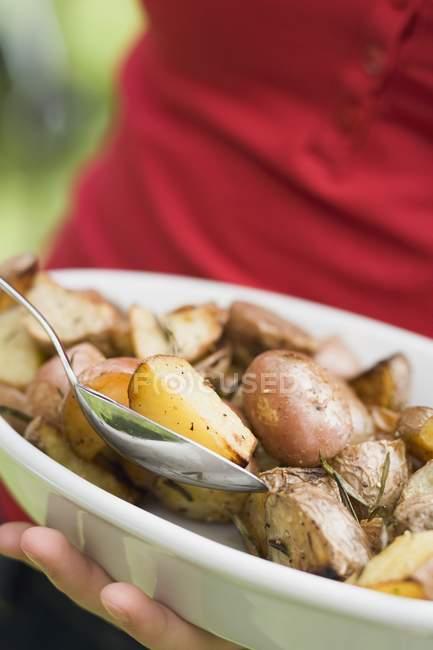 Femme tenant un plat de pommes de terre au romarin cuites au four — Photo de stock