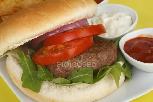 Hamburguesa con tomate y rúcula - foto de stock