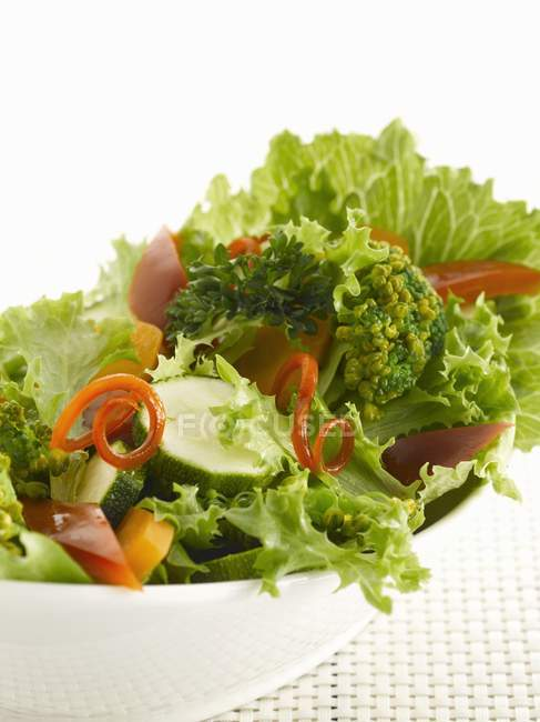 Mixed salad with lettuce, courgettes, peppers on white plate — Stock Photo