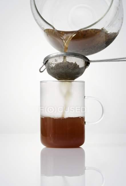 Straining tea  through a strainer — Stock Photo