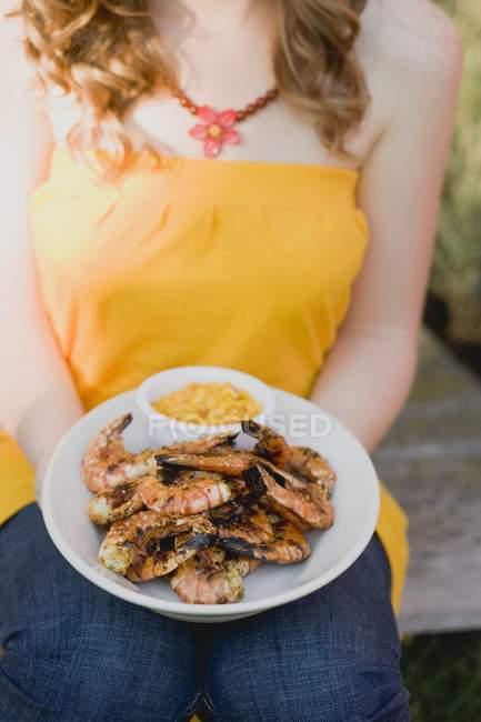 Femme tenant assiette de crevettes grillées — Photo de stock