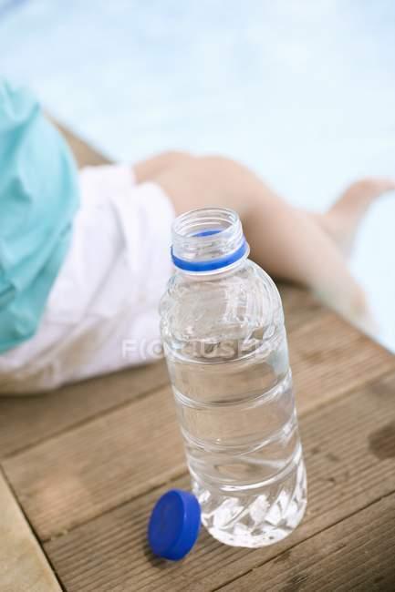 Vista de cerca del niño sentado junto a la botella de agua en el borde de la piscina - foto de stock
