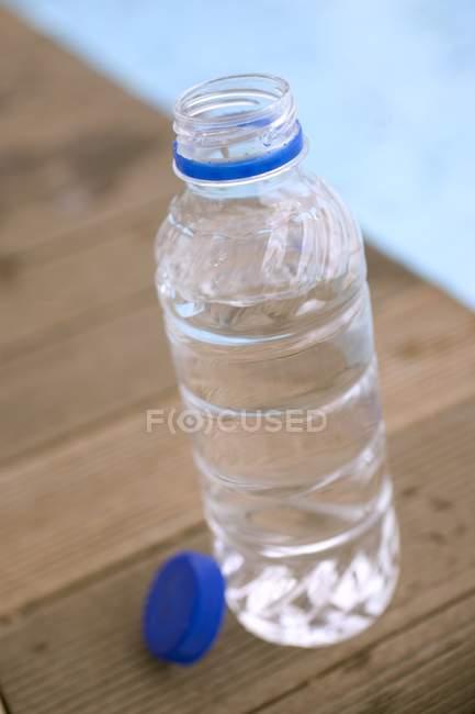 Vista de perto de uma garrafa de água aberta por piscina — Fotografia de Stock