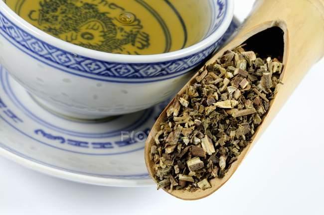 Patchouli Herb in Schaufel mit einer Tasse Tee — Stockfoto