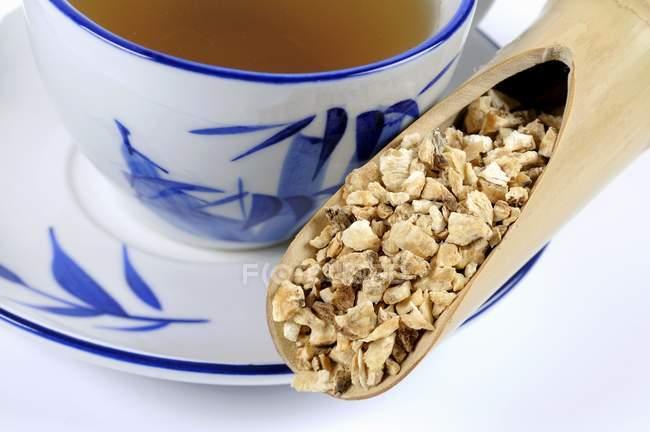 Angelikawurzel mit einer Tasse Tee — Stockfoto