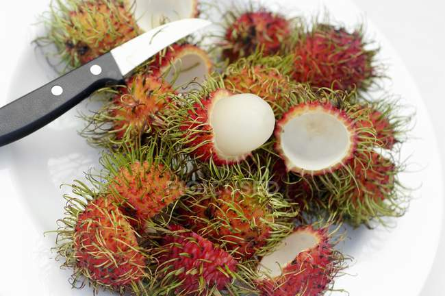 Rambutans na placa com faca — Fotografia de Stock