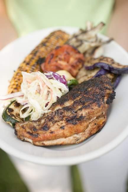 Femme tenant assiette de poulet grillé — Photo de stock