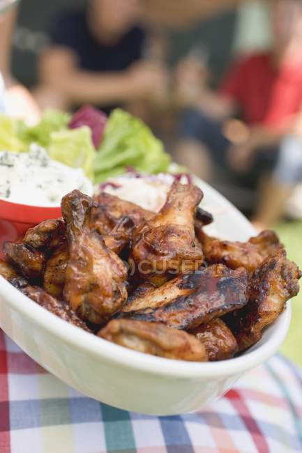 Closeup view of grilled chicken wings and salads with people in background — Stock Photo