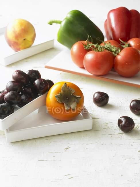 Caqui maduro fresco y cerezas - foto de stock