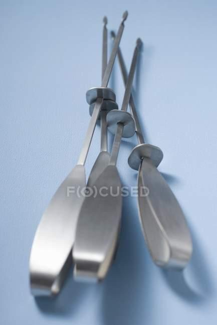 Vista close-up de quatro espetos de churrasco na superfície azul — Fotografia de Stock