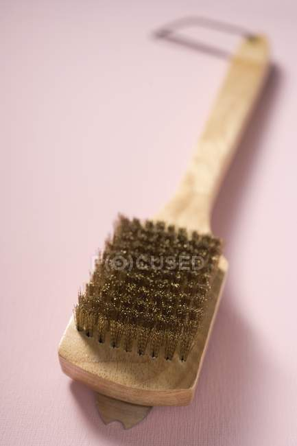 Closeup view of one wire brush on beige surface — Stock Photo