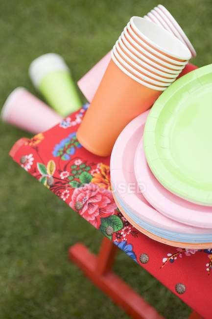 Tasses et assiettes en papier coloré sur tabouret pliant — Photo de stock