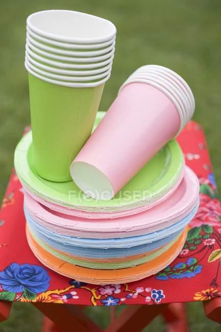 Tasses et assiettes en papier coloré sur tabouret pliant dans le jardin — Photo de stock