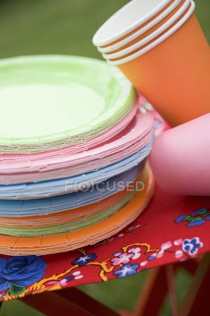 Colored paper cups and plates on folding stool in garden — Stock Photo