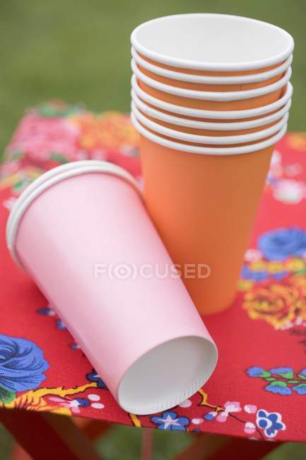 Colored paper cups and plates on folding stool u2014 Stock Photo & Colored paper cups and plates on folding stool u2014 Stock Photo ...