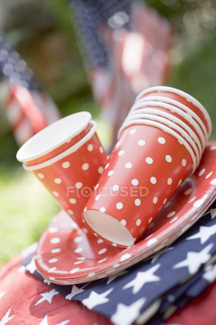 Colored stacked paper cups and plates on American flags in garden — Stock Photo