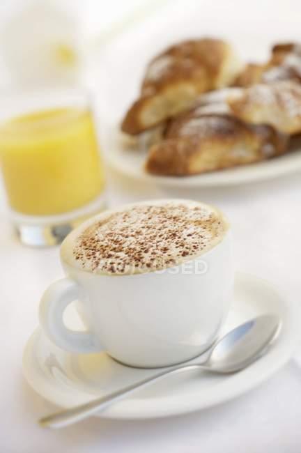 Cappuccino, orange juice and brioches — Stock Photo