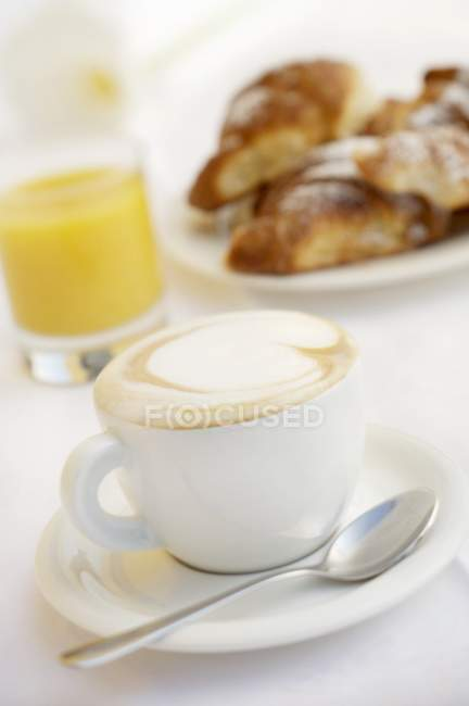 Cup of cappuccino with juice and brioches — Stock Photo