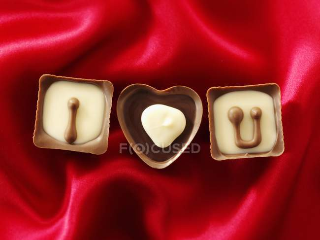 Chocolates on red fabric — Stock Photo
