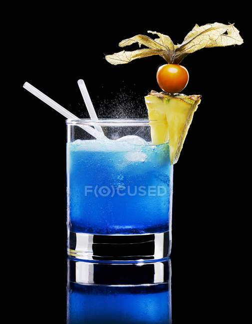Closeup view of Blue Curacao with ice, pineapple slice, physalis and drinking straws — Stock Photo