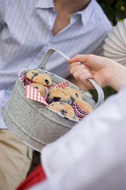 Mano sosteniendo estaño de magdalenas de arándanos - foto de stock