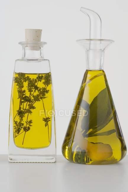 Vue rapprochée de deux huiles végétales différentes dans des bouteilles avec des herbes — Photo de stock