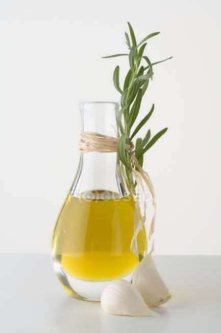 Оливковое масло в графин с чесноком — стоковое фото