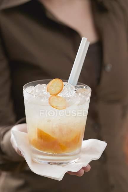 Femme tenant un cocktail avec des kumquats — Photo de stock