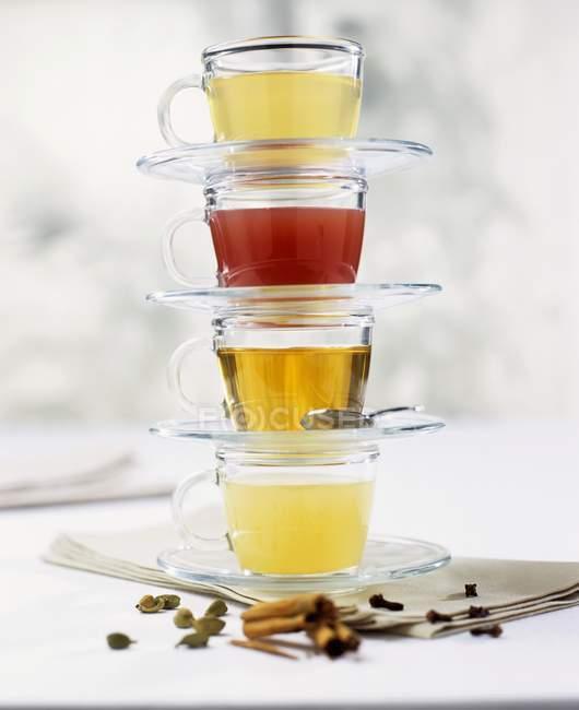 Vue rapprochée de quatre tasses et soucoupes en verre empilées avec différents thés — Photo de stock