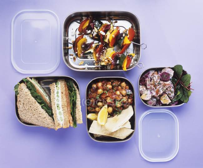 Salads, vegetable kebabs and sandwiches in lunch boxes on purple surface — Stock Photo