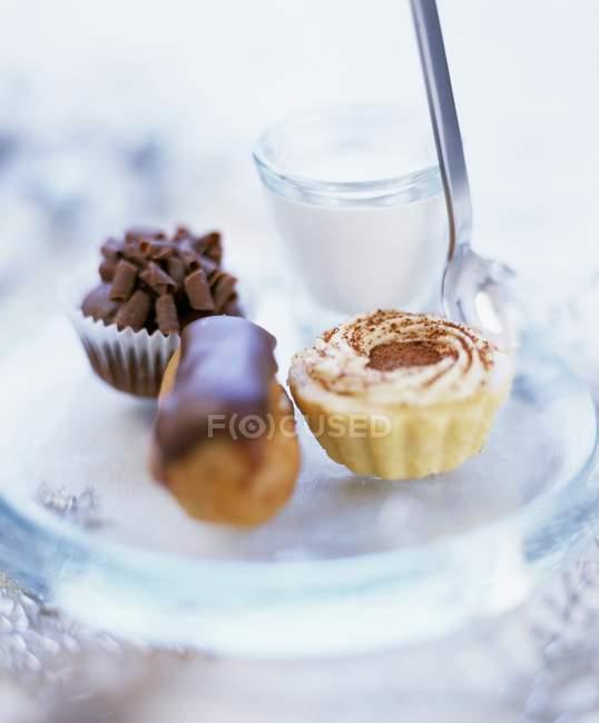 Varios pasteles pequeños en placa - foto de stock