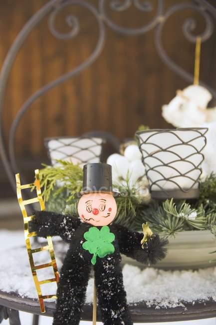 Spazzacamino con decorazioni su tavolo da giardino innevato — Foto stock