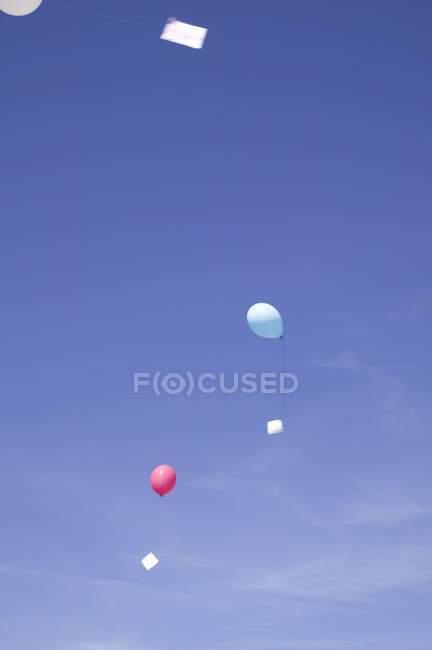 Vue diurne des ballons à air avec des lettres flottant dans le ciel — Photo de stock