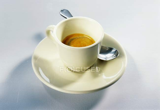 Cup of espresso with saucer and spoon — Stock Photo