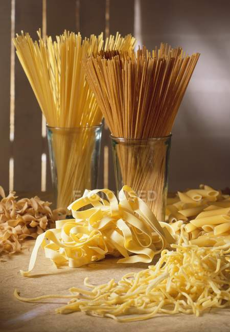 Varios tipos de pastas crudas en la tabla - foto de stock