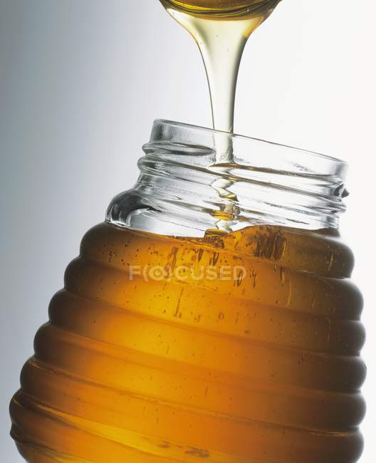 Honey in jar with spoon — Stock Photo