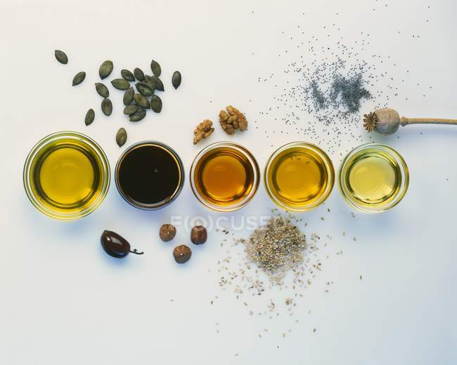 Top view of various types of oil with raw ingredients — Stock Photo