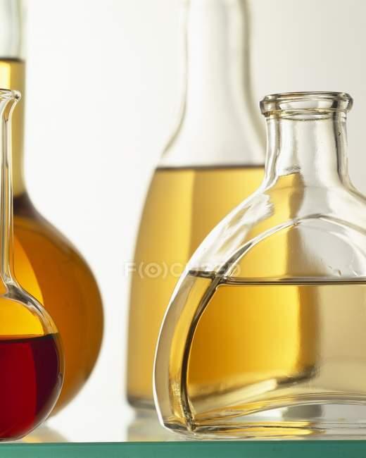 Vista de cerca de los aceites en botellas de vidrio varios - foto de stock