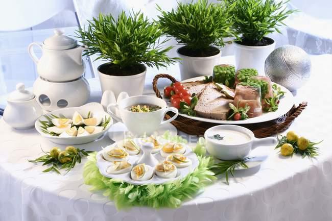 Salado desayuno de Pascua en la mesa con huevos, carne y plantas en maceta - foto de stock